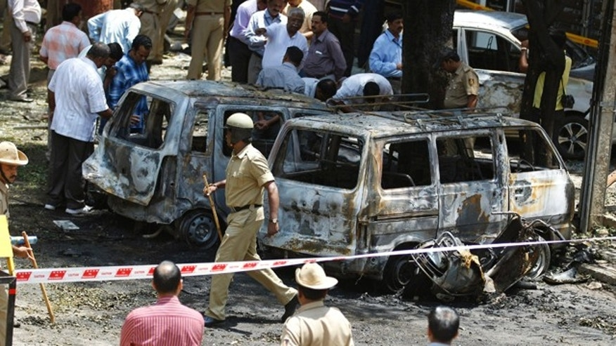April 17, 2013: Policemen and officials inspect the site of an explosion at a residential neighborhood near the office of India's main opposition Bharatiya Janata Party in Bangalore, India.