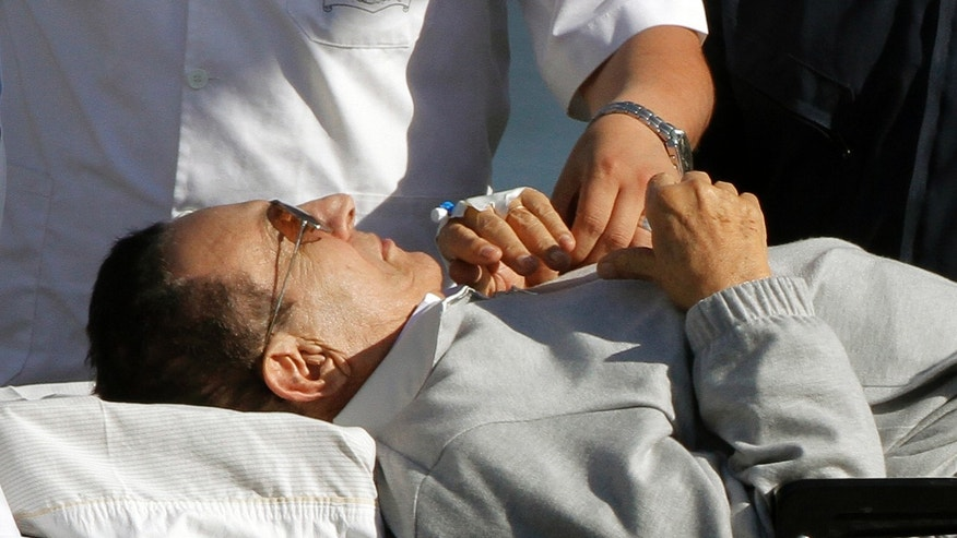 Egyptian medics escort former Egyptian President Hosni Mubarak, 84, from a helicopter ambulance after it landed at Maadi Military Hospital after he was flown form a court hearing, in Cairo, Egypt, Monday, April 15, 2013. Egypt's state news agency says deposed President Hosni Mubarak will remain in custody despite a court order to release him. The release order covers his retrial over alleged responsibility for the deaths of nearly 900 protesters during the 2011 uprising against him. Even so, he remains in custody over new corruption charges. (AP Photo/Amr Nabil)