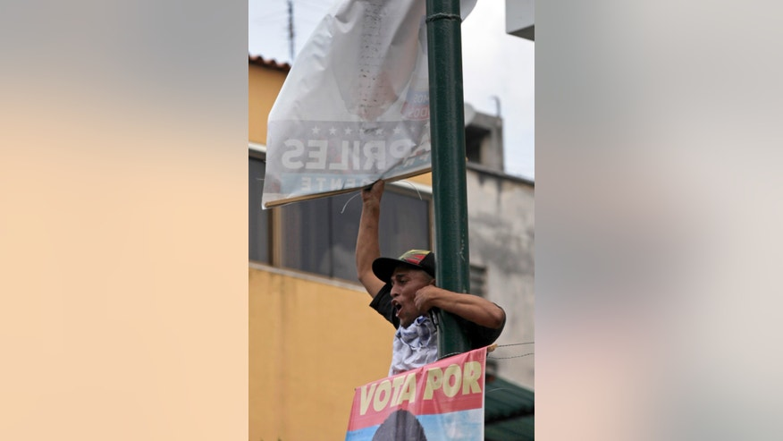 "A government ""Chavista"" supporter tears down an election poster of opposition presidential candidate Henrique Capriles in Los Teques, on the outskirts of Caracas, Venezuela, Tuesday, April 16, 2013.  President-elect Nicolas Maduro is blaming Capriles for seven deaths that the government says occurred in post-election unrest. The government has provided names of some people it says have been killed by opposition activists but has provided no evidence. Capriles is demanding a vote-by-vote recount of Sunday's presidential election. (AP Photo/Ariana Cubillos)"