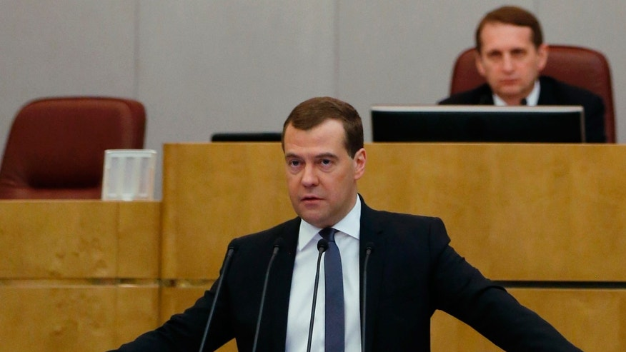 Russian Prime Minister Dmitry Medvedev addresses the State Duma, lower parliament chamber, during an annual report in Moscow on Wednesday, April 17, 2013. Parliament speaker Sergei Naryshkin listens at the background.(AP Photo/RIA Novosti, Dmitry Astakhov, Government Press Service)
