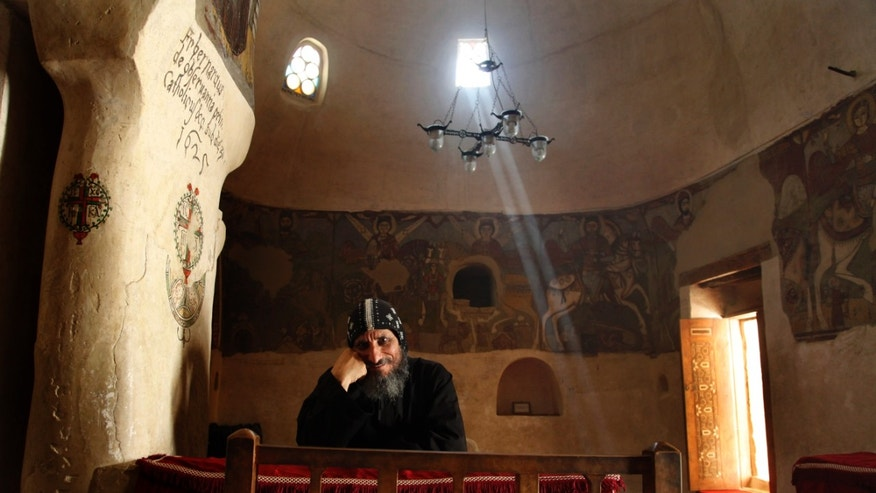In this Tuesday, April 16, 2013 photo, a monk smiles at a photographer inside a chapel dating back to the fourth century at the ancient monastery of St. Anthony in the eastern desert southeast of Cairo, Egypt. In a cave high in the desert mountains of eastern Egypt, the man said to be the father of monasticism took refuge from the temptations of the world some 17 centuries ago. The monks at the St. Anthony's Monastery bearing his name continue the ascetic tradition. But even they are not untouched by the turbulent times facing Egypt's Christians, defiantly vowing their community's voice won't be silenced amid Islamists' rising power. (AP Photo/Manoocher Deghati)