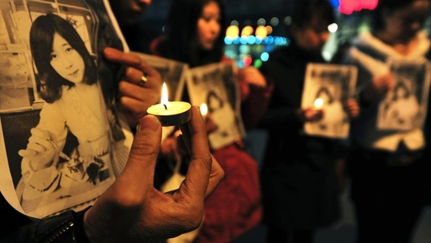 April 17, 2013: Chinese residents hold pictures of Lu Lingzi, a Boston University graduate student from China who was killed Monday in the Boston Marathon explosions, and candles to mourn for her in Shenyang in northeast China's Liaoning province. Lu was a graduate student studying mathematics and statistics and scheduled to receive her graduate degree in 2015.