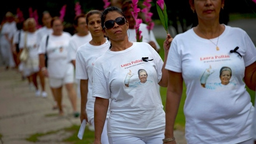 FILE - In this Oct. 14, 2012 file photo, members of Cuba's Ladies in White dissident group, wearing T-shirts with images of late co-founder of the group, Laura Pollan, participate in a march marking one year since the death of Pollan in Havana, Cuba. Members of Cubaâs Ladies in White opposition group will finally pick up Europe's top human rights prize from 2005 in person next week in Belgium, the EU and the daughter of the group's former leader said Wednesday. (AP Photo/Ramon Espinosa, File)