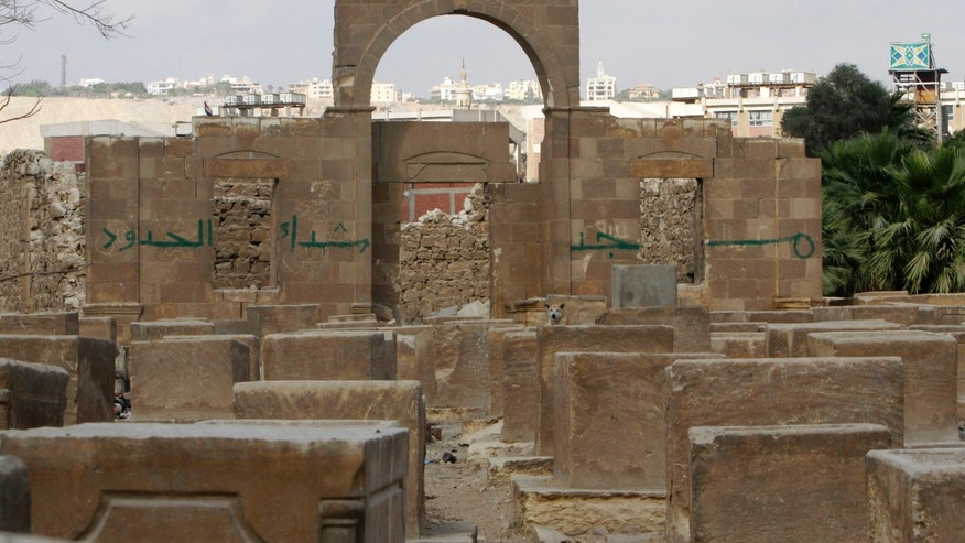 "General view showing the Jewish cemetery, in Cairo, Egypt, Thursday, April 18, 2013. The leader of Egypt's dwindling and aging Jewish community, known for her tireless work preserving synagogues and a once-sprawling Jewish cemetery, died Saturday at the age of 82. Carmen Weinstein was buried Thursday in the Bassatine cemetery she herself worked to save since 1978. It is the only Jewish cemetery left in Cairo and is the largest in Egypt. The transformation of Bassatine mirrors the dramatic changes Egypt has undergone as its population skyrocketed and poverty grew. Parts of Bassatine were turned into a garbage dump, while another area was seized by antiquities' officials. Weinstein was able to preserve a small area as a Jewish cemetery. Arabic on the walls reads, ""the mosque of the border martyrs.""  (AP Photo/Amr Nabil)"