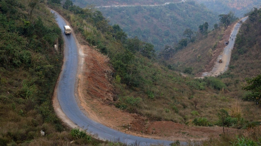 In this Feb. 23, 2013 photo, a bus, left, goes through a paved winding section of the road close to Taunggyi in central Shan state, Myanmar. The 200-mile road swerves along a mostly jungle-covered plateau of Shan state, a war-torn region that is known for drug smuggling and has been off-limits to foreigners for years. (AP Photo/Gemunu Amarasinghe)