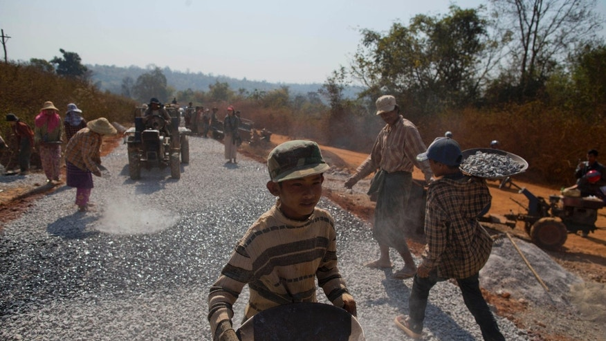 In this Feb. 20, 2013 photo, young workers carry gravel to pave a section of a road close to Mong Ne in central Shan state, Myanmar. The 200-mile road swerves along a mostly jungle-covered plateau of Shan state, a war-torn region that is known for drug smuggling and has been off-limits to foreigners for years.  (AP Photo/Gemunu Amarasinghe)