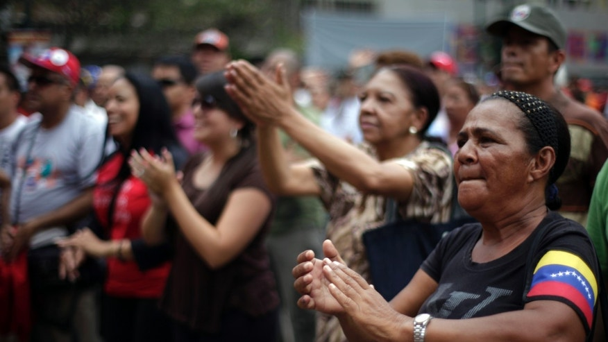 'Chavista' demonstrators, supporters of President-elect Nicolas Maduro, march in front of the National Electoral Council (CNE) in Caracas, Venezuela, Wednesday, April 17, 2013.  Opposition candidate Henrique Capriles has presented a series of allegations of vote fraud and other irregularities to back up his demand for a vote-by-vote recount for the presidential election. Maduro, the hand-picked successor of the late Hugo Chavez, was declared the winner by 262,000 votes out of 14.9 million cast, and Capriles contends the purported abuses add up to more than Maduro's winning margin. (AP Photo/Ramon Espinosa)