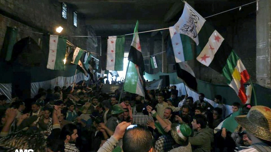 This citizen journalism image provided by Aleppo Media Center AMC which has been authenticated based on its contents and other AP reporting, shows anti-Syrian regime protesters holding Syrian revolution flags, during a rally marking the anniversary of the 1946 withdrawal of French troops from Syria, which marked the end of France's mandate of the Arab country, in the old quarter of the northern city of Aleppo, Syria, Wednesday, April 17, 2013. (AP Photo/Aleppo Media Center AMC)