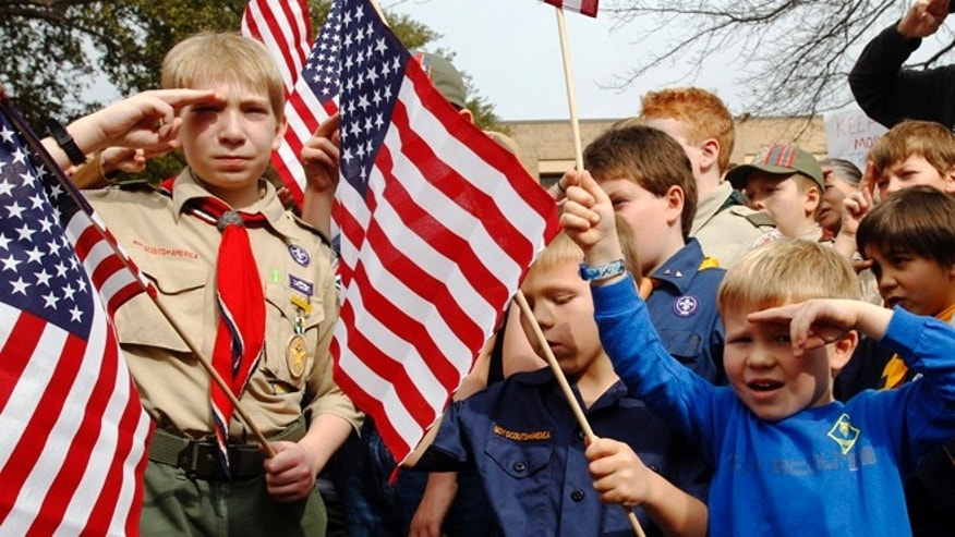 FILE - In this Feb. 6, 2013 file photo, from left, Joshua Kusterer, 12, Nach Mitschke, 6, and Wyatt Mitschke, 4, salute as they recite the pledge of allegiance during the âSave Our Scoutsâ prayer vigil and rally against allowing gays in the organization in front of the Boy Scouts of America National Headquarters in Dallas, Texas. Under pressure over its long-standing ban on gays, the BSA announced Friday, April 19, 2013, that it will submit a proposal to its National Council to lift the ban for youth members but continue to exclude gays as adult leaders. (AP Photo/Richard Rodriguez, File)