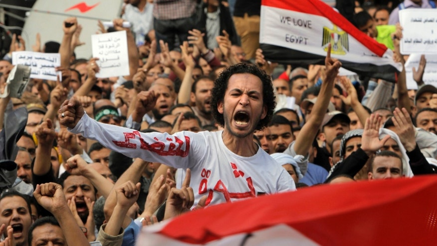 "April 19, 2013 - Egyptian Muslim Brotherhood members shout slogans during a protest in front of the Supreme Judicial Council in Cairo, Egypt. Arabic on the T-shirt reads, ""clean judiciary."""