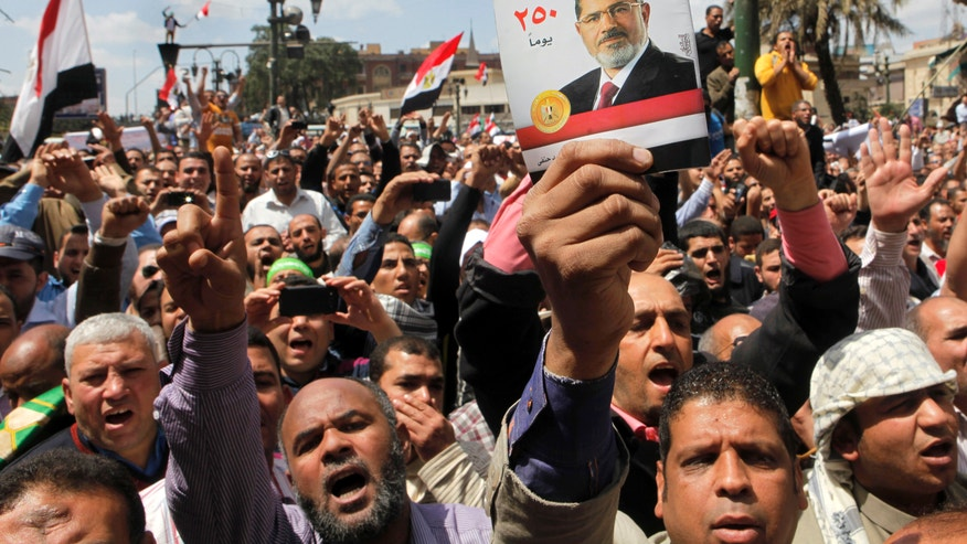 "Egyptian Muslim Brotherhood members shout slogans as they hold a book cover of Islamist President Mohammed Morsi titled ""achievements of president Morsi in 250 days"" during a protest in front of the the Supreme Judicial Council in Cairo, Egypt, Friday, April 19, 2013. Thousands of supporters of Egypt's Islamist president have taken to the streets of Cairo, calling on him to ""cleanse the judiciary."" Mohammed Morsi and the judiciary have had tense relations since he came to power in June last year. Judges accused him of trampling on their authority, while Morsi supporters charge that the judiciary is controlled by supporters of ousted President Hosni Mubarak. (AP Photo/Amr Nabil)"