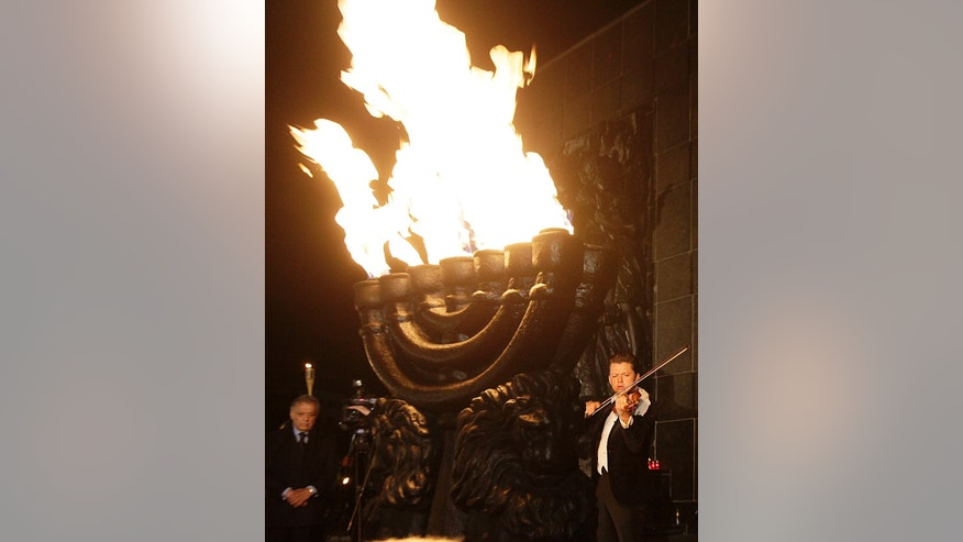 Julian Rachlin, right, the first violinist with the Israel Philharmonic Orchestra, plays a Bach sarabande in front of the monument to the fighters of the Warsaw ghetto uprising in Warsaw, Poland, on Thursday April 18, 2013. The performance was part of an evening of commemorations on the eve of the 70th anniversary of the outbreak of the 1943 revolt. (AP Photo/Czarek Sokolowski)