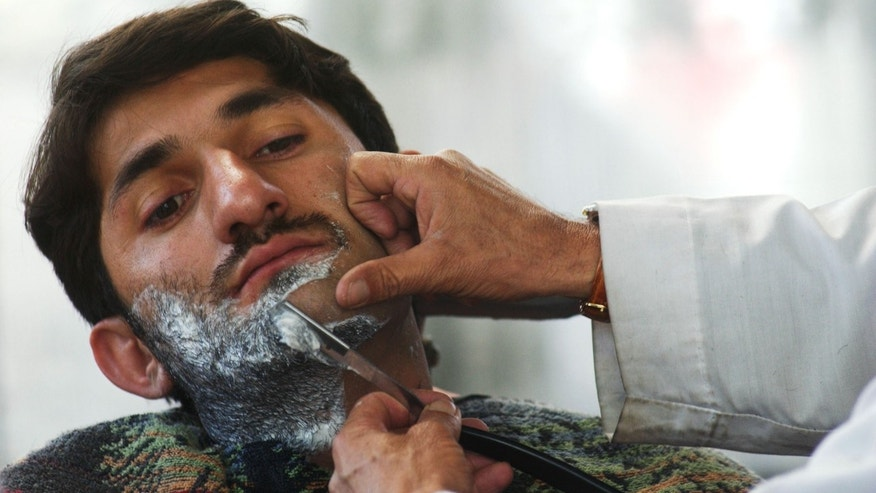 KABUL, AFGHANISTAN - MARCH 4:  An Afgan man has his beard shaved at the Fazal Mohammad Barber Shop March 4, 2003 in Kabul, Afghanistan. The trimming of beards has become fashionable and a sign of freedom. It was once it was outlawed under the Taliban rule.  (Photo by Darren McCollester/Getty Images)