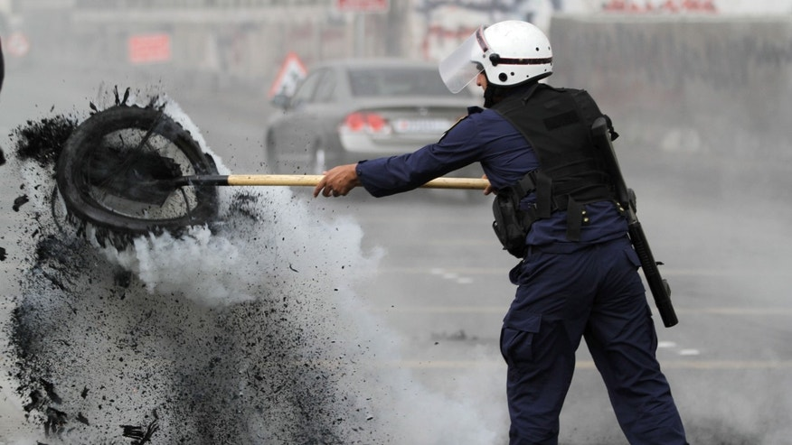 A riot policeman clears burning tires from a highway that were set ablaze by Bahraini anti-government protesters in Sehla, Bahrain, on Thursday, April 18, 2013. Organizers of Bahrain's Formula One Grand Prix, to be held Sunday, said Thursday that sporadic protests against the race and violent unrest across the Gulf nation do not pose a threat to the premier international event in the kingdom. (AP Photo/Hasan Jamali)