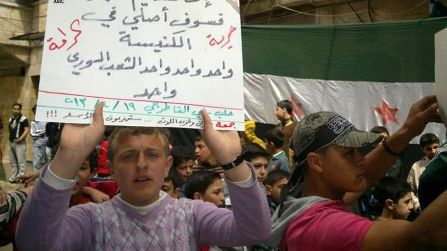 "This citizen journalism image provided by Aleppo Media Center AMC which has been authenticated based on its contents and other AP reporting, shows an anti-Syrian regime protester holds up and Arabic placard that reads: ""if you destroy my mosque I'll pray at the church, one one one the Syrian people is one, freedom, dignity,"" during a demonstration, in Aleppo, Syria, Friday April 19, 2013. Gunmen killed a government official in a Damascus restaurant, Syrian state media and activists reported Friday as regime troops and rebels fought fierce battles near the Lebanese border.(AP Photo/Aleppo Media Center, AMC)"