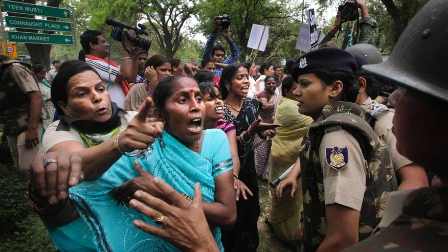 Indian women activists of India's main opposition Bharatiya Janata Party jostle with Indian police women outside ruling United Progressive Alliance chairperson Sonia Gandhi's residence during a protest against the rape of a 5-year-old girl in New Delhi, India, Sunday, April 21, 2013. The girl was raped and tortured by a man who held her in a locked room in India's capital for two days. (AP Photo/Manish Swarup)