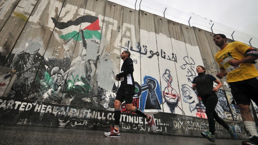 April 21, 2013: People run past the separation wall during the West Banks first marathon in Bethlehem. About 1,000 people participated in the race, which included shorter 10-kilometer and 20-kilometer options.