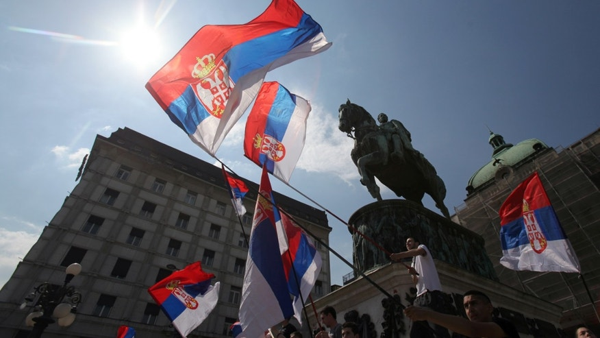 Protesters wave Serbian flags in front of the monument of late Serbian Duke Mihailo Obrenovic, during the protest of Serbian nationalist organization Dveri, in Belgrade, Serbia, Sunday, April 21, 2013. Several hundred protesters gathered to protest against recognition of Kosovo as an independent state. (AP Photo/Darko Vojinovic)