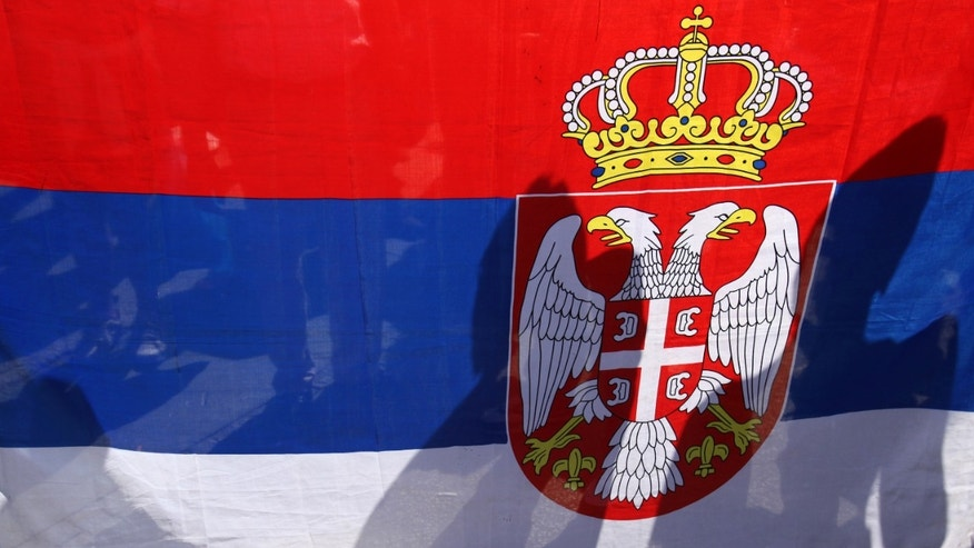 Protesters are seen through the Serbian flag during the protest of Serbian nationalist organization Dveri, in Belgrade, Serbia Sunday, April 21, 2013. Several hundred protesters gathered to protest against the recognition of Kosovo as an independent state. (AP Photo/Darko Vojinovic)