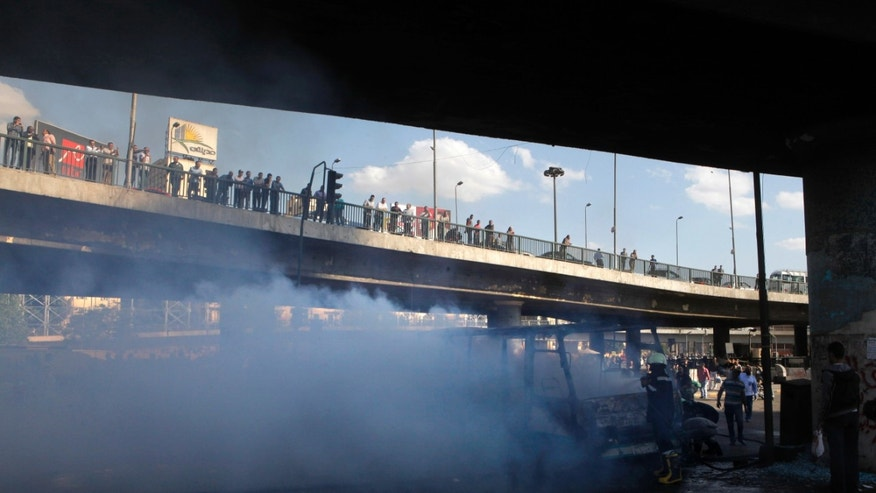 "Egyptians on a bridge watch a fire reported to be set by black block protesters on a bus belongs to Muslim Brotherhood supporters in Cairo, Egypt, Friday, April 19, 2013. Several hundred supporters and opponents of Egypt's President Mohammed Morsi are clashing near Cairo's Tahrir Square amid a rally calling on Morsi to ""cleanse the judiciary."" (AP Photo/Amr Nabil)"