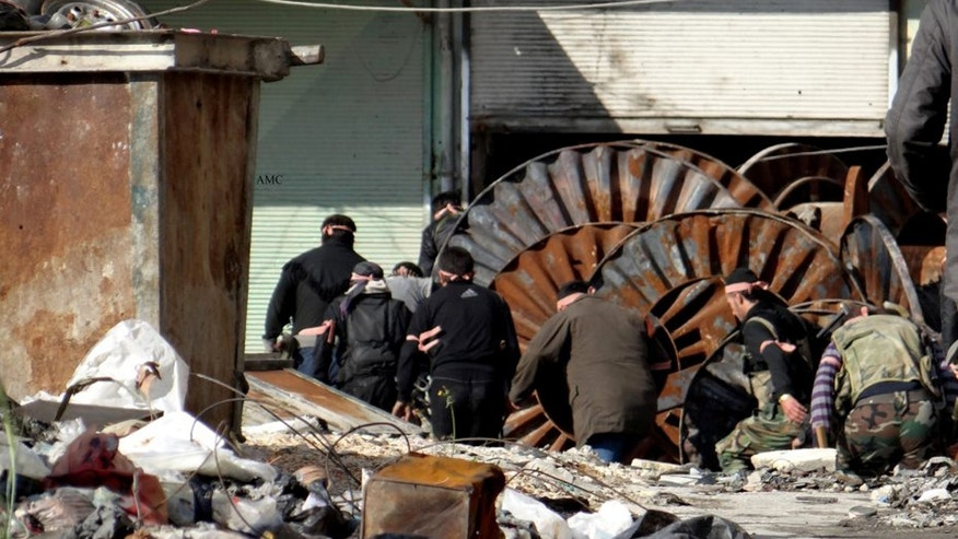 April. 21, 2013 - This citizen journalism image shows members of the free Syrian Army hiding behind scrap metal during an attack against Syrian government forces, in the neighborhood of al-Amerieh in Aleppo, Syria.