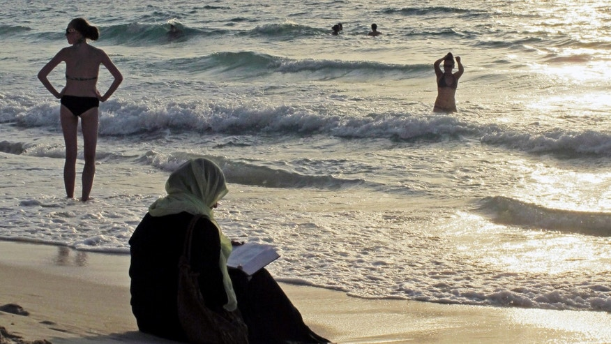 Sept. 6, 2012 - FILE photo of a woman reading the Koran on a beach as people in bikinis sunbathe and swim at sunset in Dubai, United Arab Emirates.