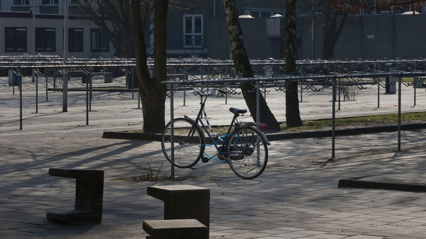 One lone bicycle is seen in the normally crowded bicycle parking area in the school yard of the closed Da Vinci College high school in the city of Leiden, west-central Netherlands, Monday April 22, 2013. All high schools in the Dutch city of Leiden have been closed for the day after police discovered an online post threatening a mass shooting. Police were patrolling in front of schools in the city Monday morning to prevent students entering as authorities attempted to track down the person who posted the threat online in an English language message. (AP Photo/Peter Dejong)
