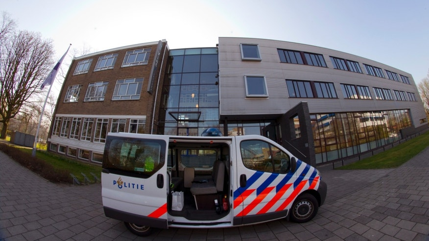 A police vehicle is parked outside the closed Da Vinci College high school in the city of Leiden, west-central Netherlands, Monday April 22, 2013. All high schools in the Dutch city of Leiden have been closed for the day after police discovered an online post threatening a mass shooting. Police were patrolling in front of schools in the city Monday morning to prevent students entering as authorities attempted to track down the person who posted the threat online in an English language message. (AP Photo/Peter Dejong)