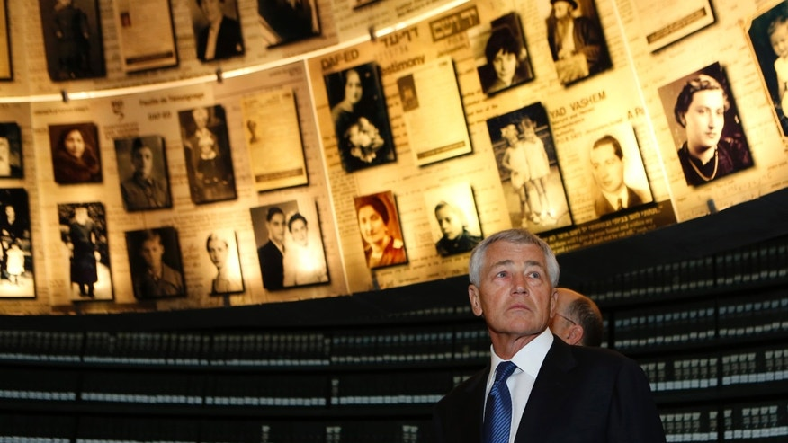 U.S. Secretary of Defense Chuck Hagel looks at pictures of Jews killed in the Holocaust during a visit to the Hall of Names at Yad Vashem's Holocaust History Museum in Jerusalem, Israel, April 21, 2013. U.S. Defense Secretary Chuck Hagel held out hope Sunday for a nonmilitary way to ending the threat of a nuclear-armed Iran, but he also emphasized Washington's willingness to let Israel decide whether and when it might strike Tehran in self-defense. (AP Photo//Baz Ratner, Pool)