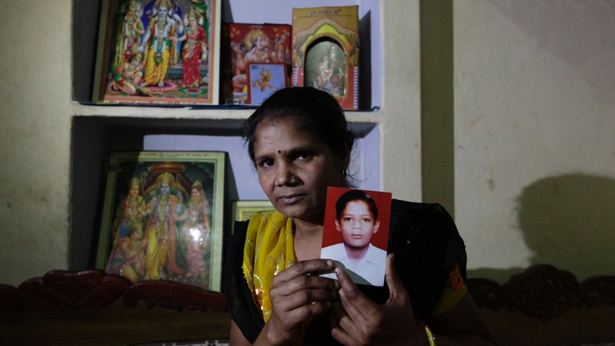 In this Monday, March 25, 2013, photo, Pravesh Kumari Singh, 36, shows a photo of her son Pankaj, 14, who went missing in 2010, in her house in New Delhi, India. Pankaj is among the more than 90,000 children who go missing in India each year. More than 34,000 of them are never found, the government said last year. (AP Photo/Manish Swarup)