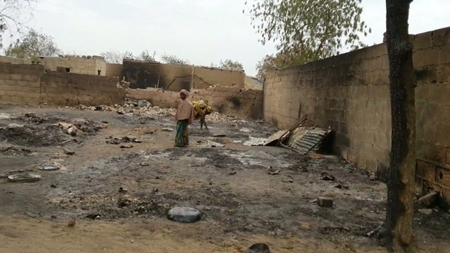 April 21, 2013: In this image shot with a mobile phone, a young girl stands amid the burned ruins of Baga, Nigeria. Fighting between Nigeria's military and Islamic extremists killed at least 185 people in a fishing community in the nation's far northeast, officials said Sunday, an attack that saw insurgents fire rocket-propelled grenades and soldiers spray machine-gun fire into neighborhoods filled with civilians.