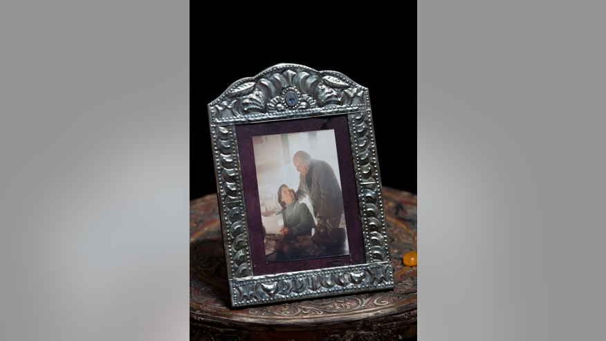 "In this April 12, 2013, a framed portrait of Clelia Luro and her late husband Jeronimo Podesta, a former bishop of Avellaneda, sits on a side table at her home in Buenos Aires, Argentina. Luro, whose romance with Podesta and eventual marriage became a major scandal in the 1960s, is such a close friend with Pope Francis that he called her every Sunday when he was Argentina's leading cardinal. She's convinced that Pope Francis will eventually lead the global church to end mandatory priestly celibacy, a requirement she says ""the world no longer understands."" (AP Photo/Natacha Pisarenko)"