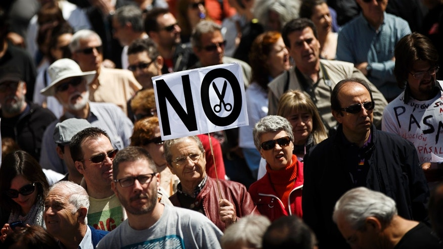 A protestor walks holding a banner reading 'No' during a demonstration against regional government imposed austerity plans to restructure and part privatize the health care sector in Madrid, Sunday, April 21, 2013. Madrid proposes selling off the management of six of 20 public hospitals and 27 of 268 health centers. Spain's regions are struggling with a combined debt of $190 billion (145 billion euro) as the country's economy contracts into a double-dip recession triggered by a 2008 real estate crash. (AP Photo/Daniel Ochoa de Olza)