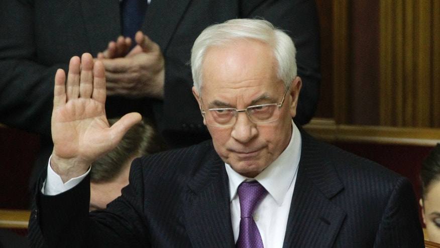 Ukraine's Prime Minister Mykola Azarov welcomes deputies during a parliament session in Kiev, Ukraine, Friday, April 19, 2013. Opposition lawmakers failed to secure enough vote to force Prime Minister Mykola Azarov to resign.(AP Photo/Sergei Chuzavkov)