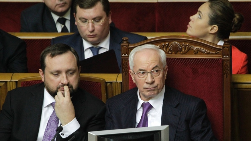 Ukraine's Prime Minister  Mykola Azarov,right, and First Vice Prime Minister of Ukraine Serhiy Arbuzov,left, attend a parliament session in Kiev, Ukraine, Friday, April 19, 2013. Opposition lawmakers failed to secure enough vote to force Prime Minister Mykola Azarov to resign.(AP Photo/Sergei Chuzavkov)