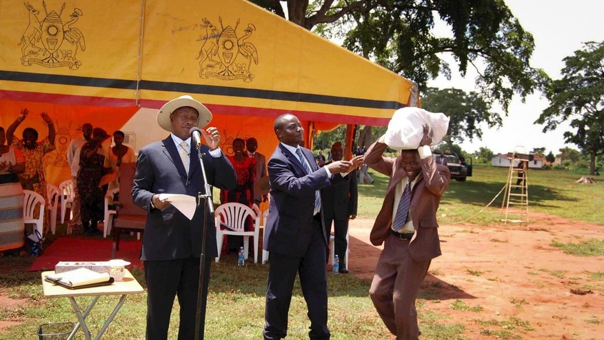 In this photo taken on Saturday, April 20 2013 and released by the Uganda Presidency, Uganda's President Yoweri Museveni, left, and State Minister for Youth and Children Affairs Ronald Kibuule, center, hand over what the president's office said was a sack of money containing 250 million Ugandan shillings - about $100,000 - to an unidentified member of a partisan group of youths, right, in Kaliro district east of the capital Kampala, in Uganda. It's become an infamous photo in Uganda. The country's leader looks on in bemusement as a young man bends low to carry a sack filled with a donation from the president _ almost $100,000 in cash. The money is a donation from President Yoweri Museveni to a partisan group of youths in eastern Uganda, where he struggles to win votes in national elections, and activists and opposition politicians are seizing upon the moment as a blatant example of political corruption in Uganda. The picture, which was distributed by the president's office after the event last weekend, was meant to highlight Museveni's generosity toward a group of youth. Instead it has focused attention on Museveni's profligacy during political tours and what some say is his role in fueling graft in the East African country that he has led since 1986.  (AP Photo/Uganda Presidency)