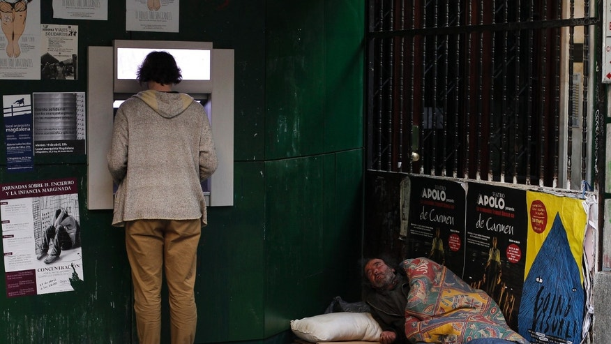 A man uses an ATM machine as a homeless man begs for alms from his makeshift bed in Madrid, Spain, Monday, April 22, 2013. The 2012 figures from Eurostat, the European Union's statistics office, showed Monday that in spite of efforts to get a handle on its debts, Spain saw its budget deficit rise to 10.6 percent of GDP in 2012 from 9.4 percent the year before as the country took US dlrs 52 billon (40 billion euro) in rescue loans to help its banks. Excluding the rescue funds, Spain says its deficit last year improved to just under 7 percent, above the initially pledged target of 6.3 percent. (AP Photo/Andres Kudacki)
