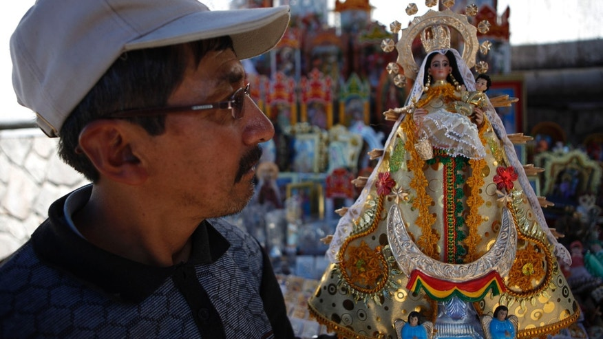 A vendor of religious icons holds a small-scale statue of the Virgin of Copacabana in front of the Basilica of Our Lady of Copacabana, in Copacabana, Bolivia, Tuesday, April 23, 2013. Thieves propped a ladder against a back wall of the 16th-century shrine early Monday morning and entered through a window, stripping the Virgin of Copacabana, Bolivia's patron saint, of her crown and golden ornaments, according to the priest in charge of the church. Colonial churches south of Bolivia are seeing a wave of thefts. (AP Photo/Juan Karita)