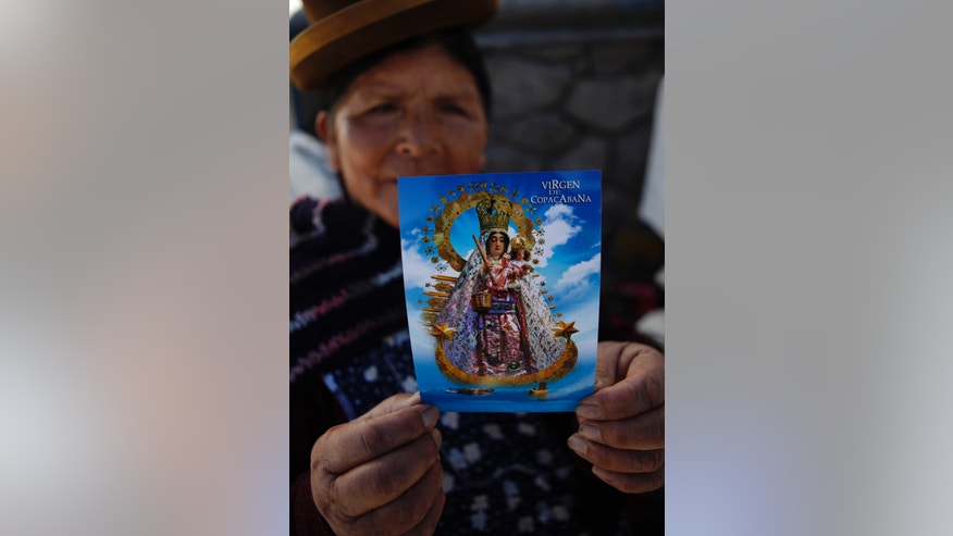 A parishioner expresses her sadness over a robbery that occurred at the Basilica of Our Lady of Copacabana, as she holds up a post card showing the Virgin of Copacabana statue, in Copacabana, Bolivia, Tuesday, April 23, 2013. Thieves propped a ladder against a back wall of the 16th-century shrine early Monday morning and entered through a window, stripping the Virgin of Copacabana, Bolivia's patron saint, of her crown and jewels, according to the priest in charge of the church. Colonial churches south of Bolivia are seeing a wave of thefts. (AP Photo/Juan Karita)