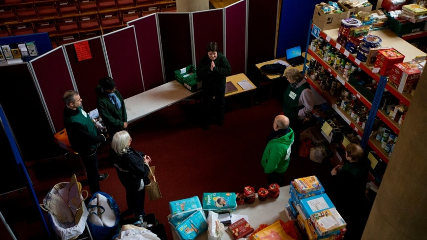 "In this photo taken Friday, April 5, 2013, Elizabeth Maytom, top center, the foodbank project leader for the Brixton and Norwood areas of London leads a group prayer with volunteers at the start of a distribution session at a food bank in St Luke's Church in the West Norwood area of London. It's possible that official figures on first quarter economic growth, to be released Thursday, could put the country back in recession. It would take the smallest statistical variation to put the figure in negative territory which would place the country in recession, another recession _ the third since the 2008 financial crisis _ and is already being referred to with foreboding in the media as a ""Triple Dip"". (AP Photo/Matt Dunham)"
