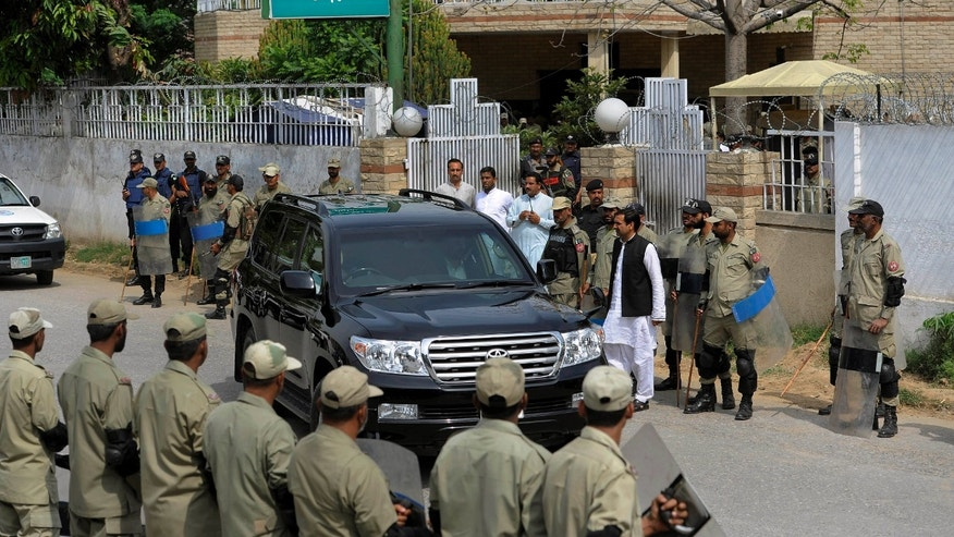 April 23, 2013: Paramilitary troops stand guard as a vehicle carrying Pakistan's former President and military ruler Pervez Musharraf leaves an anti-terrorism court in Rawalpindi, Pakistan. Musharraf appeared before the anti-terrorism court over the assassination of former prime minister Benazir Bhutto's case, officials said.
