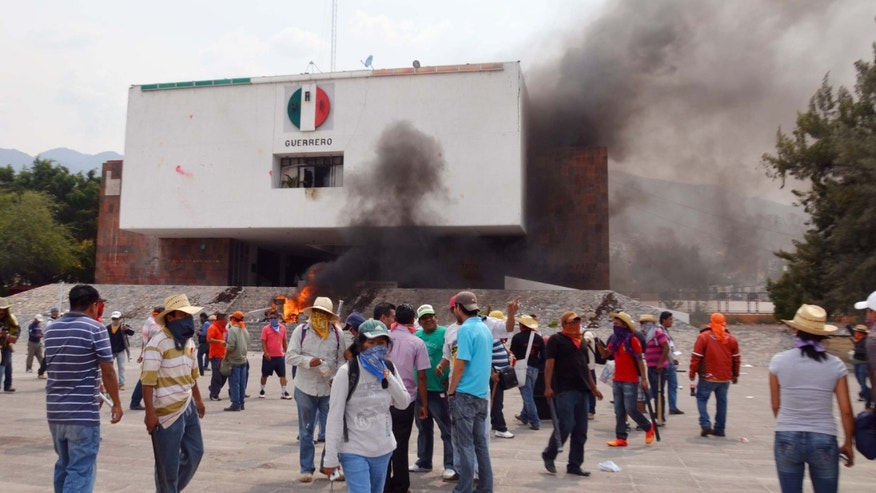 Protesting teachers stand outside of the regional offices of the Revolutionary Institutional Party, PRI, after they attacked the building causing significant damage in Chilpancingo, Mexico, Wednesday, April 24, 2013. Protesting against President Enrique Pena Nieto's education reform project, thousands of elementary and high school teachers in Guerrero, one of the country's poorest and worst-educated states, walked out more than a month ago, turning hundreds of thousands of children out of class and since have launched an increasingly disruptive string of protests. (AP Photo/Alejandrino Gonzalez)