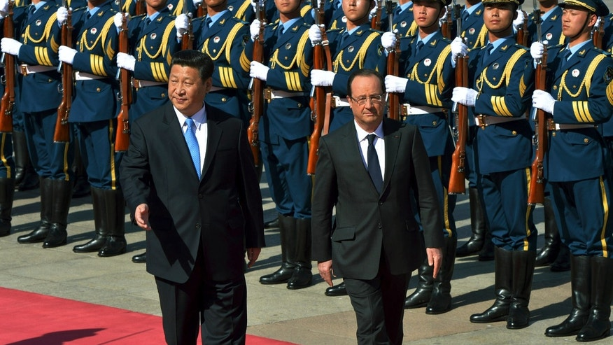 Chinese President Xi Jinping, left, gestures while escorting French President Francois Hollande as they review an honor guard during a welcome ceremony outside the Great Hall of the People in Beijing Thursday, April 25, 2013. Hollande is in China on a visit aimed at shoring up trade relations amid France's worsening economic woes.  (AP Photo/Mark Ralston, Pool)
