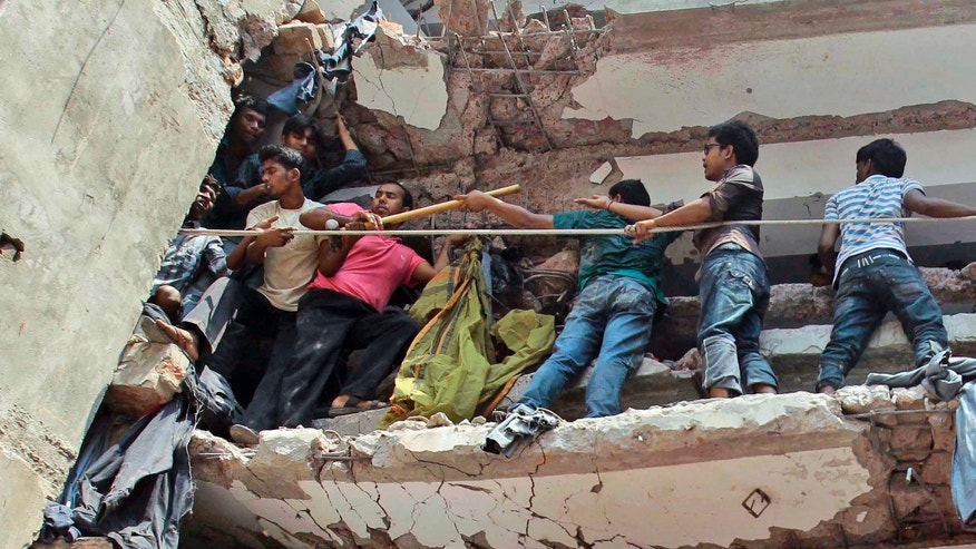 Bangladeshi rescuers squeeze through a gap to help pull out survivors spotted in the debris of a building that collapsed in Savar, near Dhaka, Bangladesh, Wednesday, April 24, 2013. An eight-story building housing several garment factories collapsed near Bangladesh's capital on Wednesday, killing dozens of people and trapping many more under a jumbled mess of concrete. Rescuers tried to cut through the debris with earthmovers, drilling machines and their bare hands. (AP Photo/A.M.Ahad)