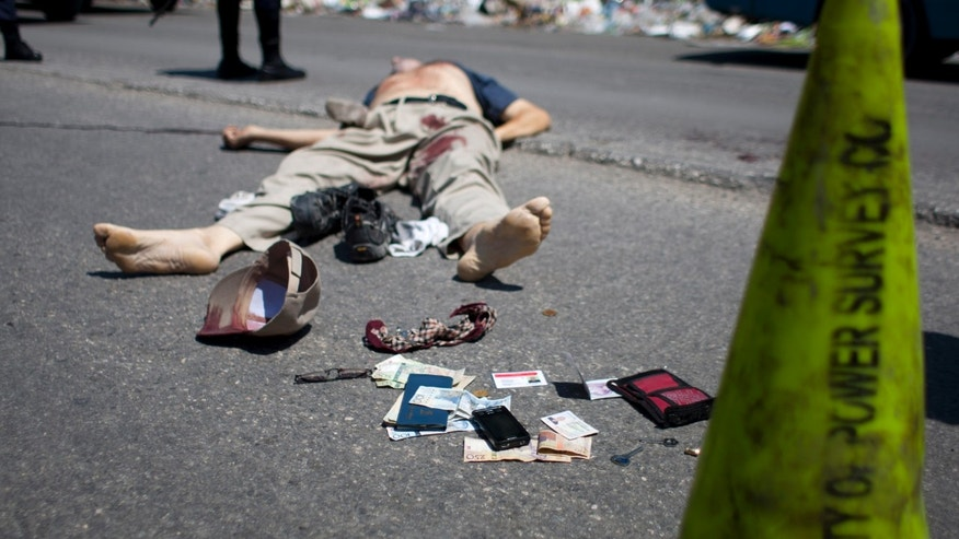 Cash and personal belongings that were placed there by police lay next to slain Canadian priest Richard E. Joyal in the Delmas district of Port-au-Prince, Haiti, Thursday, April 25, 2013. Police inspector Aladin Jean-Louis says that the 62-year-old Joyal had just withdrawn (Canadian) $1,000 from a bank when two men on a motorcycle approached and grabbed a bag he was carrying, and the passenger shot him three times in the back. Authorities later found the $1,000 in Joyal's wallet in his pocket and placed it at his feet. The contents of Joyal's billfold included a driver's license showing he was from Quebec. Another identification card showed he was a priest who worked as an administrator for a Canadian congregation in the Delmas district of Port-au-Prince. (AP Photo/Dieu Nalio Chery)