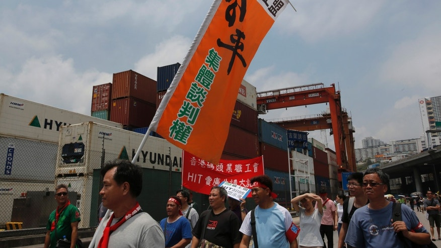 Striking port workers march outside container ports during a protest in Hong Kong Thursday, April 25, 2013. Hong Kong dockworkers have briefly blocked a road and refused to stop camping out at a tower owned by the city's richest man, as their bitter strike was close to dragging into a second month. About 300 striking workers protested Thursday by walking slowly on the road in front of the Asian financial hub's container ports. The protest lasted several hours and left trucks backed up for several kilometers.  (AP Photo/Vincent Yu)