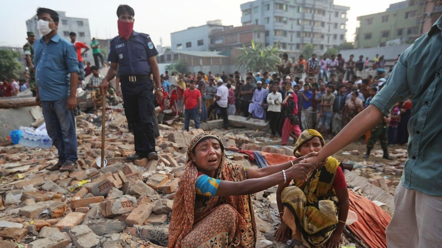 A Bangladeshi woman weeps as she waits at the site of a building that collapsed Wednesday in Savar, near Dhaka, Bangladesh, Friday, April 26, 2013. The death toll reached hundreds of people as rescuers continued to search for injured and missing, after a huge section of an eight-story building that housed several garment factories splintered into a pile of concrete.(AP Photo/Kevin Frayer)