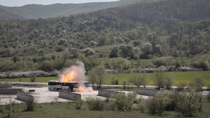 A bus explodes near Ihtiman, on Friday, April 26, 2013, as Bulgarian investigators stage a re-enactment of the bus bombing that killed five Israeli tourists, the bus driver and the alleged perpetrator at the Burgas airport in July. The experiment aimed to provide more details about the attack and was staged at a police compound. (AP Photo/Valentina Petrova)