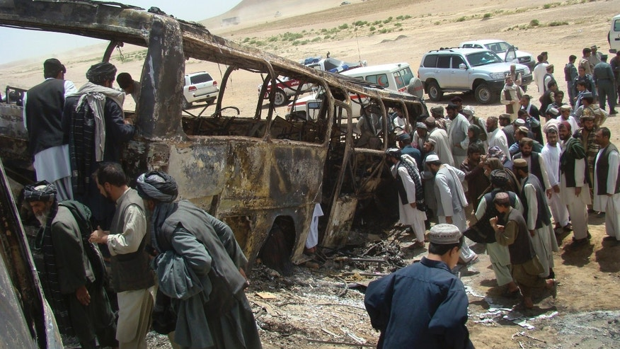 April 26, 2013 - Afghan men surround a burned bus after it collided with the wreckage of a truck that was attacked by Taliban insurgents in Maiwand district, Afghanistan.