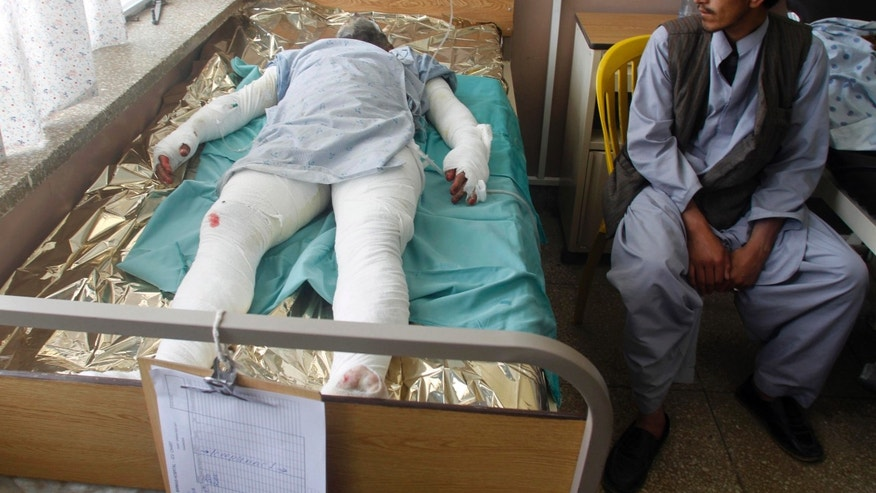 April 26, 2013 - An Afghan man visits a wounded relative in the hospital in Kandahar, Afghanistan, after a bus collided with the wreckage of a truck that was attacked by Taliban insurgents in Maiwand district.